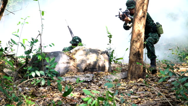Two Fully Equipped and Armed Soldiers appearing and looking the enemy before patrolling to tropical forest