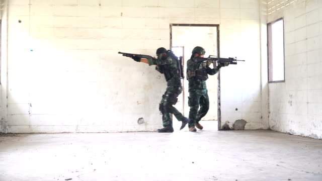 two fully Equipped and Armed Soldiers patrol in unknown house