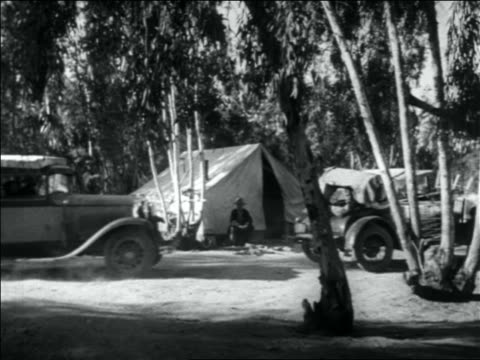 vidéos et rushes de b/w 1936 two fully loaded cars pulling into migrant worker camp stopping by tent - 1936