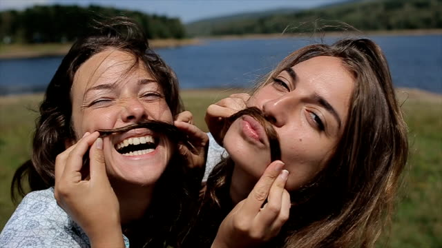 two funny girls make mustache with hair - happy human face stock videos & royalty-free footage