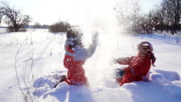 Two funny kids throwing snow together