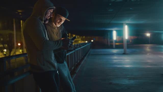 slo mo 夜に市内のスマートフォンを使用して 2 つの暴力団 - 犯罪者点の映像素材/bロール