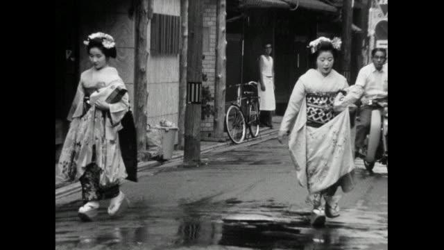 two geisha women walk on wet city street in japan; 1966 - femininity stock videos & royalty-free footage