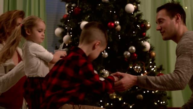 vídeos y material grabado en eventos de stock de dos generaciones familiares colgantes adornos en su árbol de navidad juntos - adorno de navidad
