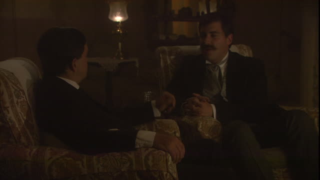 two gentlemen share drinks and conversation in a parlor. - reenactment stock videos & royalty-free footage