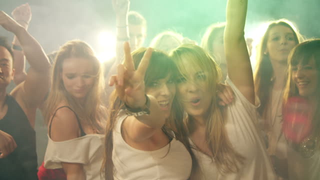 stockvideo's en b-roll-footage met two gils having fun in disco - vredesteken handgebaar