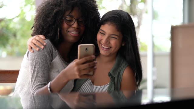 Two girl friends laughing at cellphone