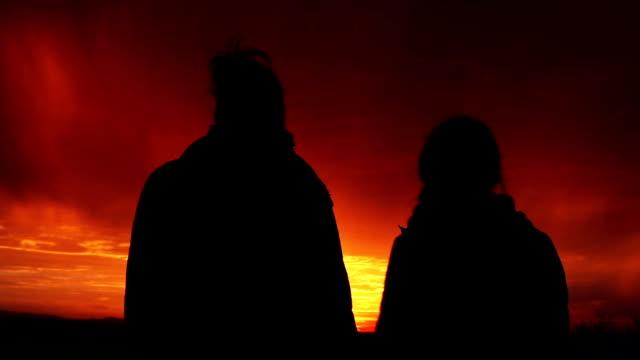 Deux filles amoureux en regardant le coucher de soleil