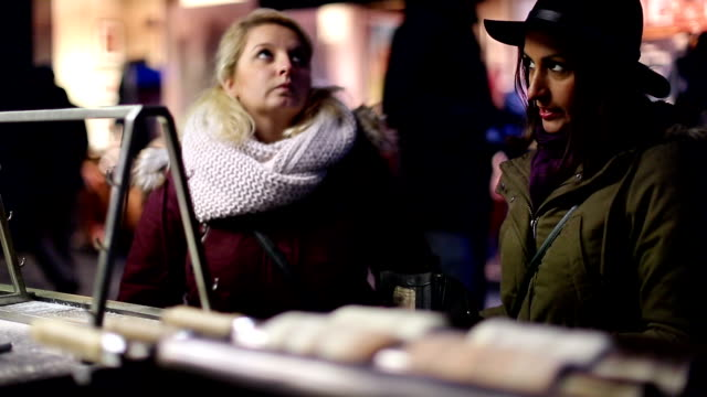 Two girlfriends buying trdelnik on street kiosk