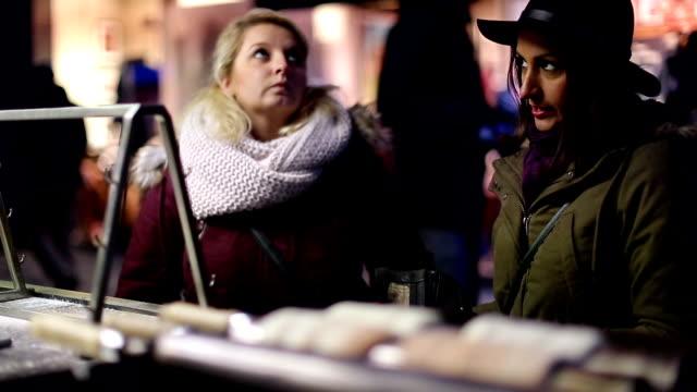 two girlfriends buying trdelnik on street kiosk - prague stock videos and b-roll footage