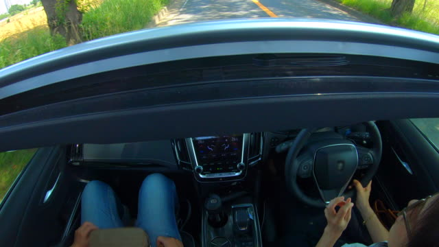 Two girlfriends driving together in a car / sunroof