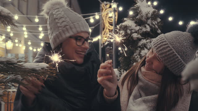 two girlfriends holding sparklers during new year celebration - human face video stock e b–roll