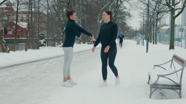 stockvideo's en b-roll-footage met twee vriendinnen in sportkleding zijn stretching - peter snow