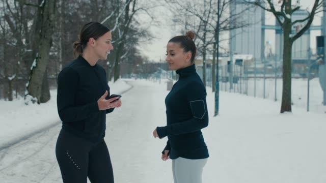 スポーツ服の2人のガールフレンドがストレッチしている - 女子トラック競技点の映像素材/bロール