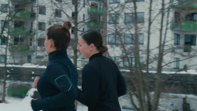 two girlfriends jogging in sports clothes - peter snow stock videos & royalty-free footage