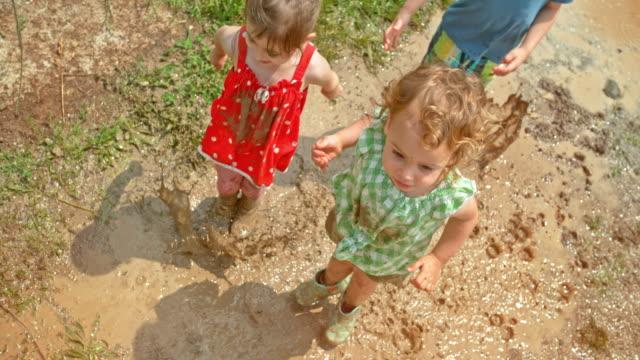 vidéos et rushes de slo mo deux filles et un garçon sautant dans la flaque d'eau boueuse sous le soleil - 4 5 ans