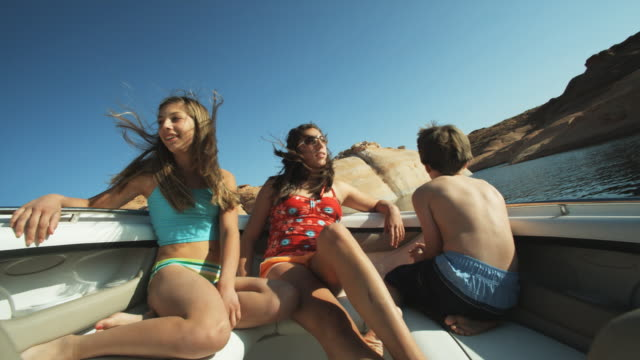 two girls and a boy on a boat