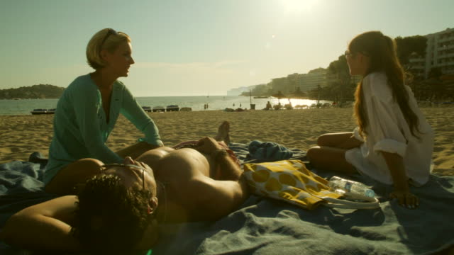 tu ws two girls and guy relaxing at beach,mallorca - haar nach hinten stock-videos und b-roll-filmmaterial