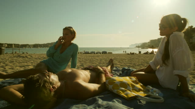 pan ws two girls and guy relaxing at beach,mallorca - haar nach hinten stock-videos und b-roll-filmmaterial
