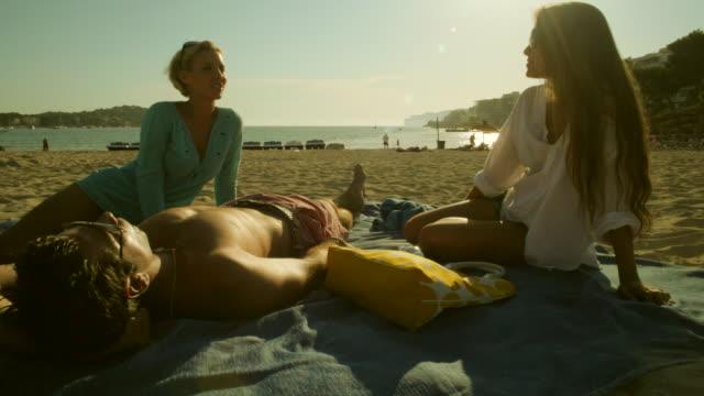 tu ws two girls and guy relaxing at beach,mallorca - マヨルカ点の映像素材/bロール