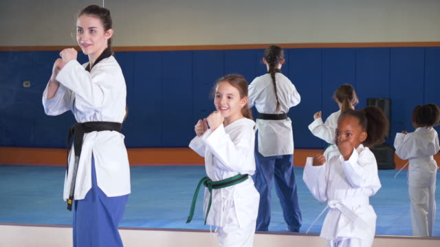 two girls and teacher in taekwondo class - bow pose stock videos & royalty-free footage