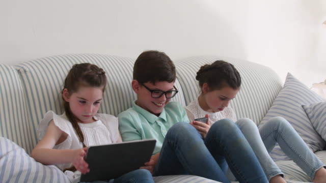 Two girls and their brother using digital tablet and phone on sofa