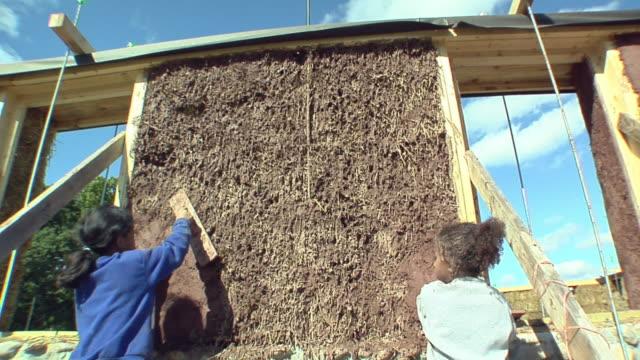 ms two girls (4-5, 6-7) applying adobe mud mixture to wall of straw house under construction, grass lake, michigan, usa - adobe bildbanksvideor och videomaterial från bakom kulisserna