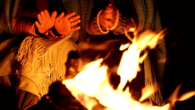 vidéos et rushes de deux filles se réchauffent par un incendie dans la forêt d'hiver - foyer de cheminée