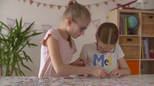 two girls assembles big bright puzzle at the table - puzzle stock videos & royalty-free footage