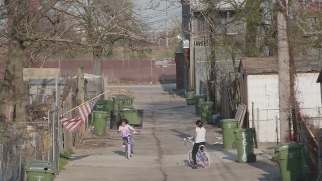 two girls bike in an alley in the curtis bay neighborhood during the covid-19 pandemic on april 6, 2021 in baltimore, maryland. there have been 2 170... - family with two children stock videos & royalty-free footage