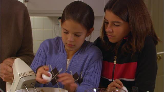 cu, two girls (10-11) breaking egg into bowl of cookie dough in kitchen, grandmother in background - 10 11 år bildbanksvideor och videomaterial från bakom kulisserna