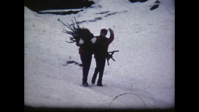 1966 two girls carrying small Christmas tree through snow