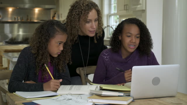 two girls doing homework together in kitchen with mom helping. - family with two children stock videos & royalty-free footage