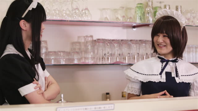 ms two girls dressed as a maids laugh and talk in a tokyo maid cafã© / tokyo, japan - 扮装点の映像素材/bロール