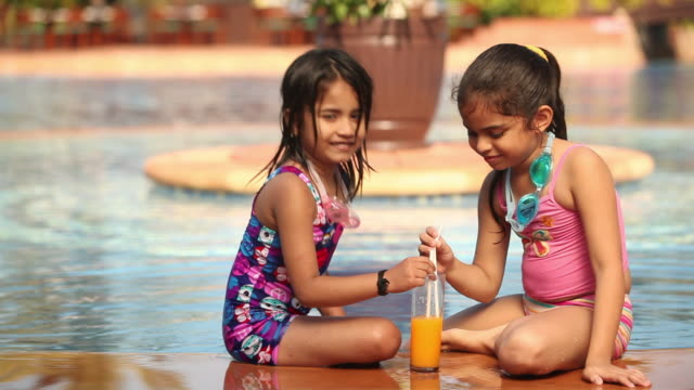 two girls drinking juice on the ledge of a swimming pool  - saft stock-videos und b-roll-filmmaterial