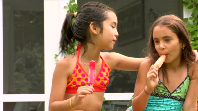 stockvideo's en b-roll-footage met ms two girls eating frozen popsicles side by side and giving thumbs up / sherman, ct, usa - likken