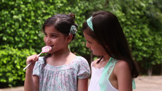 two girls eating lollipop - lollipop stock videos and b-roll footage