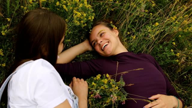 vídeos y material grabado en eventos de stock de dos chicas disfrutan al aire libre, en la hierba en la naturaleza - generation z