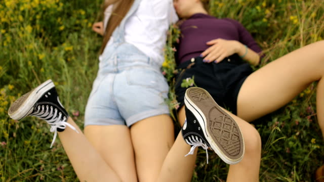 two girls enjoy outdoors, on the grass in nature - human limb stock videos & royalty-free footage
