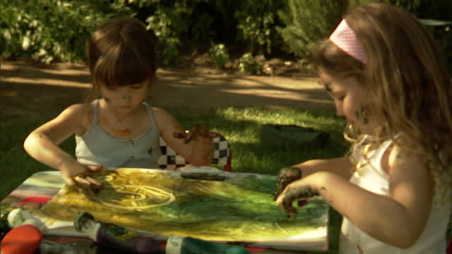 CU, Two girls (4-5) finger painting in garden