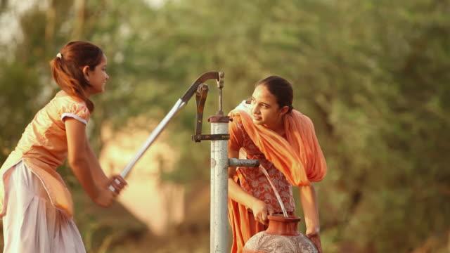 Two girls fliing pot of water from handpump, Faridabad, Haryana, India