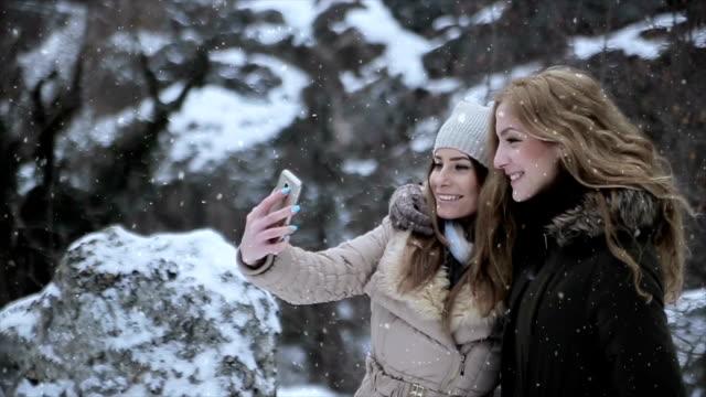 twee meisjes vrienden neem foto's voor een wintervakantie, met mobiele telefoon