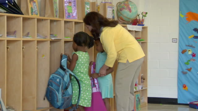 ms two girls hanging their backpacks in cubbyholes and holding hands with their teacher in preschool classroom / san antonio, texas, usa - hanging stock videos & royalty-free footage