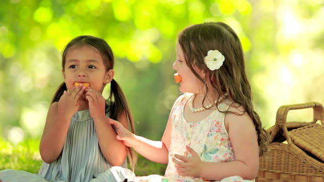 Two girls have fun eating fruit