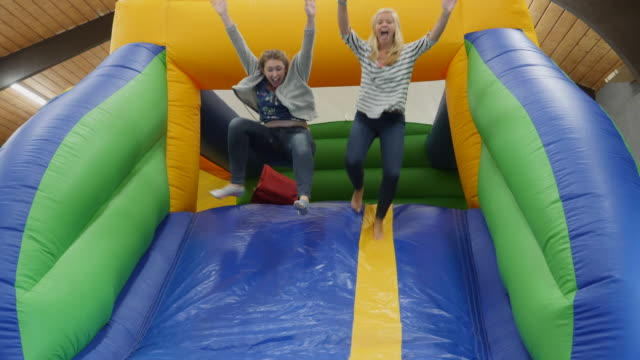 4k: two girls having fun on a bouncy castle inflatable slide - inflatable stock videos and b-roll footage