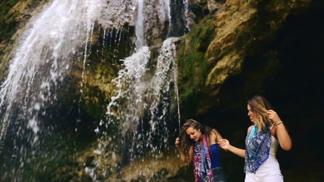 Two girls having fun under waterfall