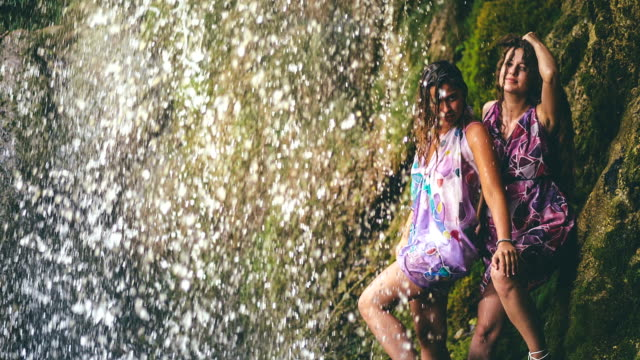 Two girls having fun under waterfall