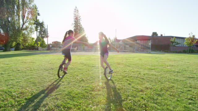 ms slo mo two girls holding hands riding unicycles in circle on grass field near school - only girls stock videos and b-roll footage
