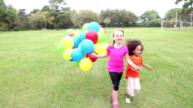 vídeos de stock e filmes b-roll de two girls holding hands running with bunch of balloons - 4 5 anos