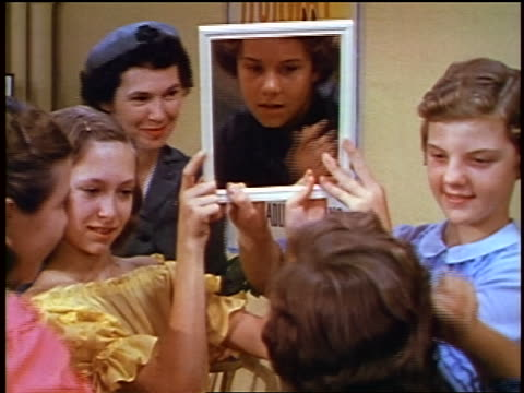 1957 two girls holding mirror for other girl combing her hair / feature